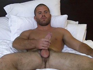 Muscled bald gay hunk wanks his fat hard cock on high abut on